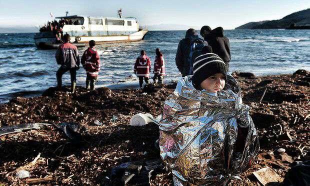 کودکی که در پتوی اضطراری پیچیده شده و همراه با سایر پناهندگان به ساحل جزیره لِسبُس در یونان رسیده است