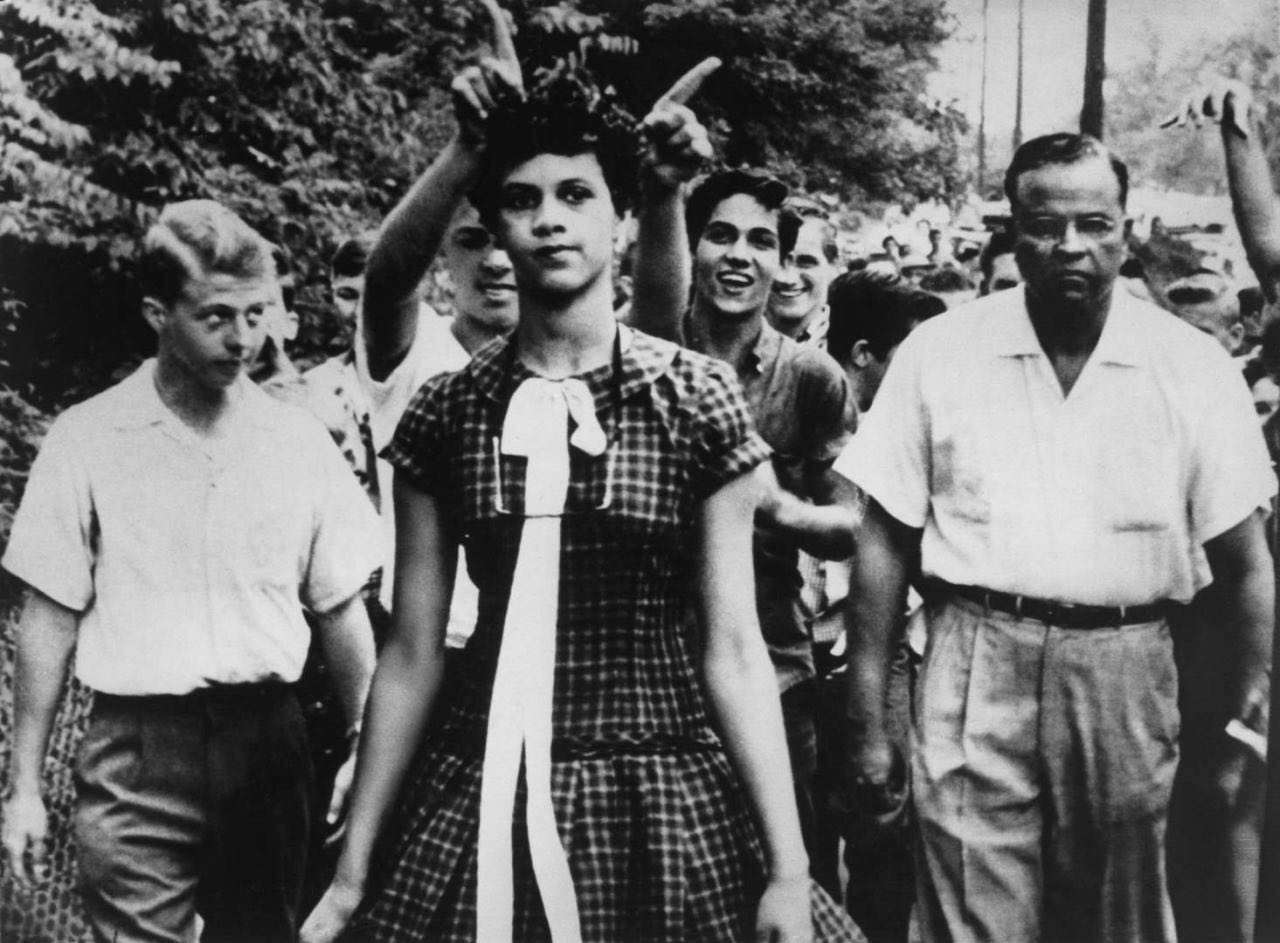 اولین دختر سیاه پوستی آمریکایی که وارد دبیرستان شد. این عکس او را در حالی که همکلاسیهای سفید پوستش  او را مسخره میکنند نشان میدهد؛ آمريكا-1960