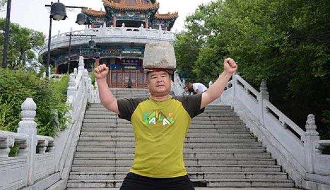 """یک مرد چینی به نام """"سونگ یان"""" (53 ساله) برای کاهش وزن به صورت روزانه سنگی به وزن 40 کیلوگرم را روی سرش حمل می کند"""