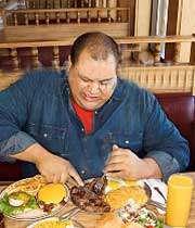 مردی چاق در حال غذا خوردن