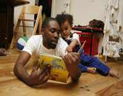 father reading book to his baby
