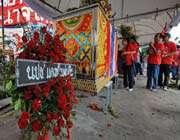 les chemises rouges thaïlandaises ont défilé à bangkok avec les cercueils de victimes des violences de samedi