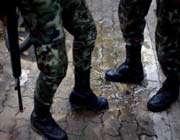 des militaires thaïlandais nettoient les taches de sang sur le lieu de l'attentat à la grenade, à bangkok, le 8 mai 2010.
