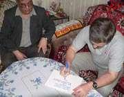 الکساندر کالری در حال نوشتن پیام تبریک پرتاب ماهواره امید در کنار برزو