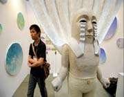 a man walks past an artwork from japanese artist takashi yamauchi at the art fair tokyo 2011 in tokyo.